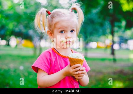 Poco funny girl bionda mangiare blu dolci gelato in una cialda cup su un verde sfondo estiva nel parco. cosparso Foto Stock