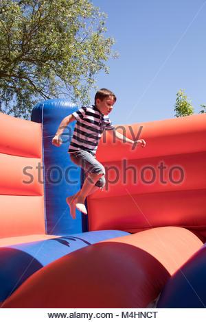 Little Boy salta su un castello gonfiabile Foto Stock