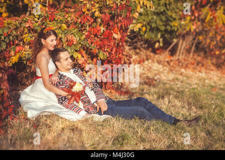 Lo Sposo è seduta sul prato in autunno park appoggiata contro una sposa Foto Stock