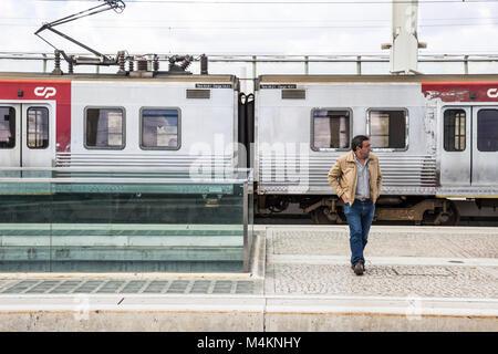 Un uomo su una piattaforma alla stazione Oriente a Lisbona, Portogallo. Foto Stock