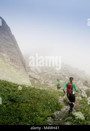 Gli atleti corrono lungo il sentiero di montagna a bad foggy meteo Foto Stock