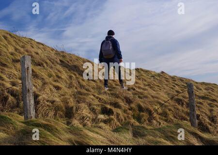 Giovane escursionista su una ruvida pendio erboso al di là di un vecchio rotto filo spinato. Cruden Bay, Aberdeenshire, Foto Stock