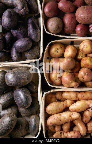 Varietà di materie organiche non cotte patate diversi tipi e colori rosso, giallo, viola in cesti di mercato. Sfondo di cibo. Vista superiore, vicino fino Foto Stock