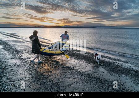 Un giovane lanciando un gonfiabile reft al tramonto off Alki Beach, Seattle, Washington, Stati Uniti d'America
