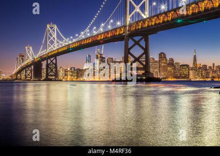 Classic vista panoramica del famoso Oakland Bay Bridge con lo skyline di San Francisco illuminata nella bellissima twilight dopo il tramonto in estate, Califo Foto Stock