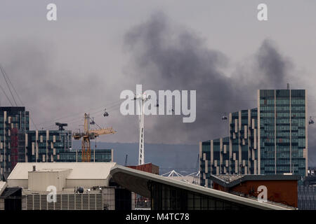Londra, Regno Unito. 18 Febbraio, 2018. London Fire: fumo nero sorge su edifici da east London con Emirates Airline Foto Stock