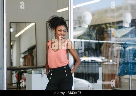 0343d33f32f7 ... Abito sorridente designer nel suo negozio di stoffa con abiti firmati  sul display. Imprenditrice donna