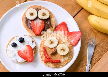 Frittelle con facce buffe decorazioni per bambini. Un sano frittelle di frutta Per i pasti dei bambini Foto Stock