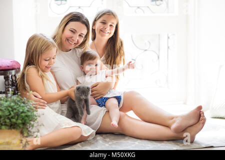 Giovane donna graziosa e figlie giocando con il gattino in ambienti interni Foto Stock