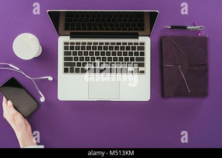 Colpo ritagliata della moderna imprenditrice utilizza lo smartphone al lavoro sulla superficie viola Foto Stock