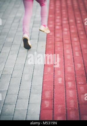 Bambina in esecuzione sul marciapiede Foto Stock