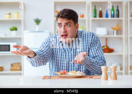 Pranzo Per Marito : Giovane marito mangiare cibo insipido a casa per il pranzo foto