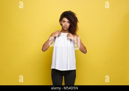 Bella attraente americano africano donna posting e vestito in su la sua t-shirt bianco. Il giallo di sfondo per Foto Stock