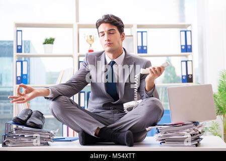 L imprenditore seduto sulla parte superiore della scrivania in ufficio Foto Stock