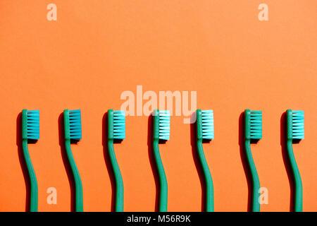 Gli spazzolini da denti verde in fila, su orange con spazio di copia