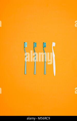 Vista superiore del verde e gli spazzolini da denti bianchi in fila, isolati su Orange