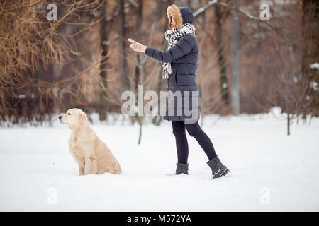 Immagine della ragazza in giacca nera del cane di formazione nel parco innevato Foto Stock