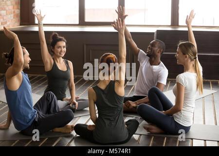 Emozionato multirazziale persone alzando le mani insieme a yoga di gruppo Foto Stock
