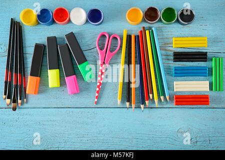 Forniture scolastiche (forbici, vernici, creta per modellare, marcatori matite) su blu sullo sfondo di legno. Vista dall'alto. Copia dello spazio. Foto Stock