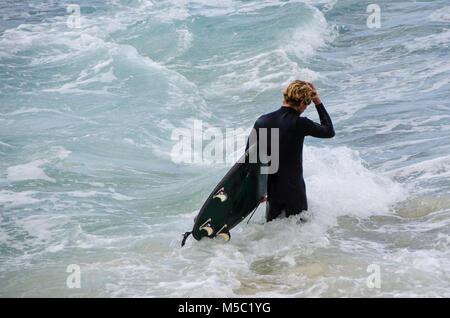 Surfista maschio a piedi attraverso le onde con la tavola da surf. Libertà e aspettativa come maschio passeggiate Foto Stock