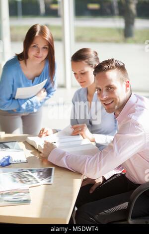 Ritratto di fiducioso giovane imprenditore a discutere con i colleghi di sesso femminile alla scrivania in ufficio Foto Stock