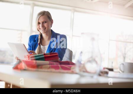 Ritratto di fiducioso giovane imprenditrice utilizzando tavoletta digitale alla scrivania in ufficio creativo Foto Stock