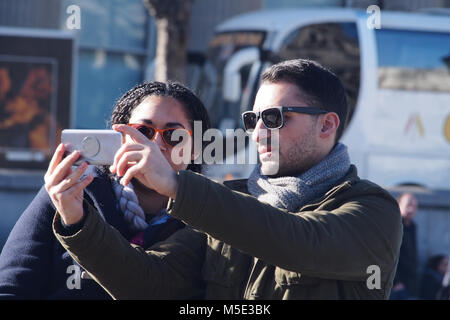 Una giovane coppia di prendere una selfie con uno smartphone indossando occhiali da sole in inverno il sole in Trafalgar Foto Stock