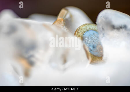 Congelati New British una sterlina moneta fino vicino all'interno della macro di cubetti di ghiaccio. Foto Stock