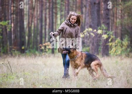 Giovane donna attraente giocando con il pastore tedesco cane all'aperto nel parco di autunno Foto Stock