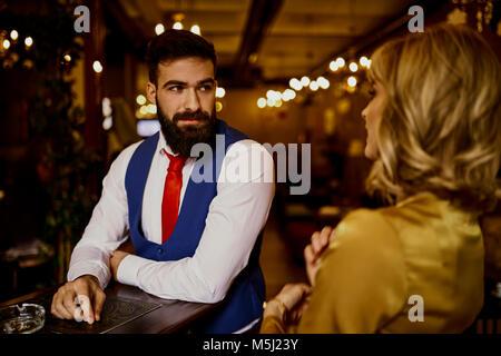 Moda giovane uomo che guarda la donna in un bar Foto Stock