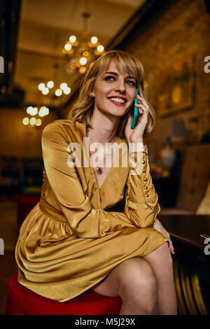 Ritratto di sorridente donna elegante in un bar sul telefono cellulare