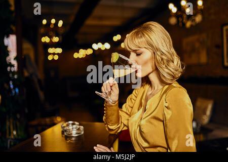 Donna elegante bere un cocktail in un bar Foto Stock