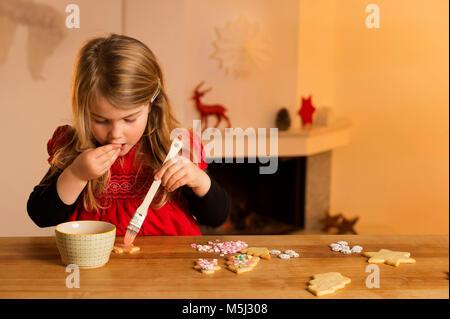 Bambina la farcitura di biscotti di Natale con centinaia e migliaia Foto Stock