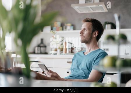 Uomo serio con la compressa seduta in cucina con i piedi fino alla ricerca a distanza Foto Stock