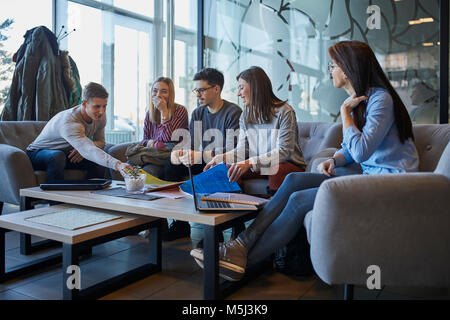 Gruppo di amici seduti insieme in un cafe con il computer portatile e i documenti Foto Stock