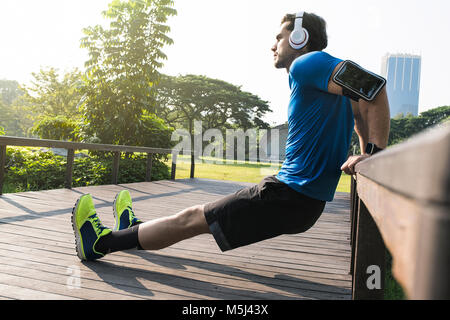 Runner con cuffie facendo push-up nel parco urbano Foto Stock
