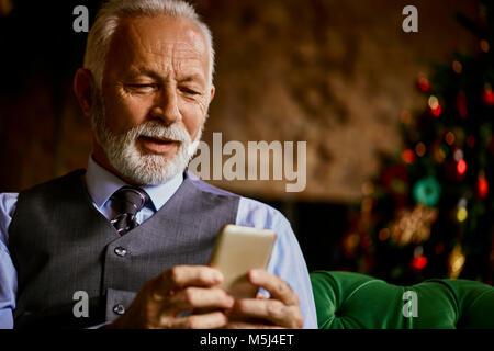Elegante uomo senior tramite telefono cellulare Foto Stock
