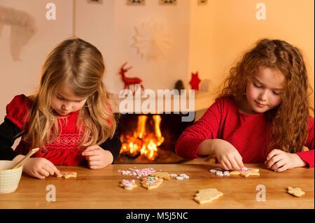 Bambine la farcitura di biscotti di Natale con centinaia e migliaia Foto Stock