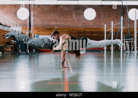 Due uomini facendo acrobazie in palestra Foto Stock