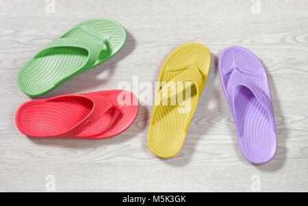 Verde, rosso, giallo e viola flip flop su una tavola di legno sfondo bianco Foto Stock