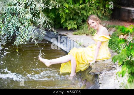 La Russia, Mosca, Izmaylovsky Park, 27 agosto 2017. International Photo Festival.Una ragazza allegro dall'acqua. Una ragazza del lago di schizzi i suoi piedi wit