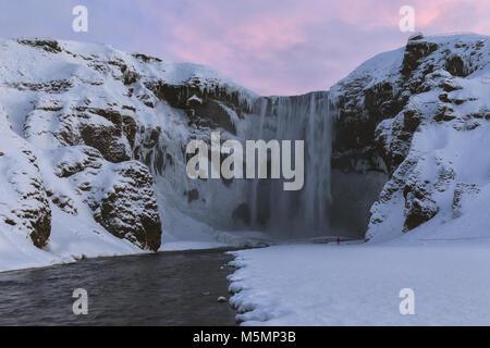 Skogafoss cascata in un inverno di sunrise, Islanda Foto Stock