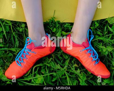 Donna gambe in stivali rossi con un blu lacci delle scarpe sull'erba e giallo sfondo scozzese Foto Stock