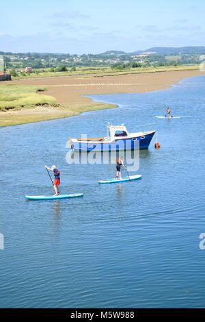 Gruppo di persone godono di stand up paddle imbarco sul fiume Ax vicino a Seaton in Devon Foto Stock