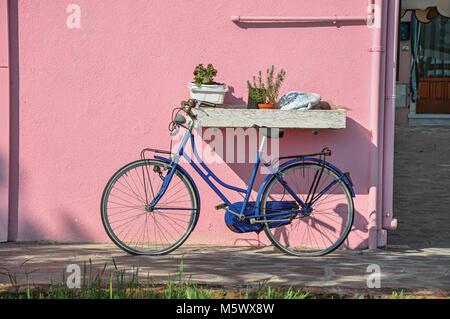 Close-up di bicicletta appoggiata contro la parete colorata in una giornata di sole a Burano, una graziosa cittadina Foto Stock