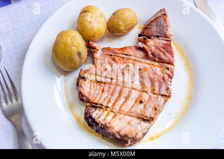 Succosa bistecca di tonno con patate servita su piastra bianca Foto Stock