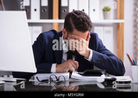 Giovane uomo che soffre di mal di testa che lavorano in ufficio con Bill su scrivania Foto Stock