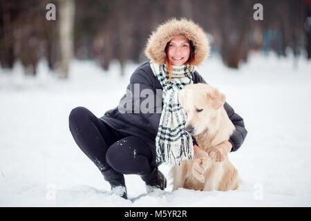 Immagine della ragazza in giacca nera accovacciata accanto al cane in inverno Foto Stock