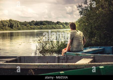 Ragazzo adolescente solitaria contemplazione uno scenario paesaggistico sulla barca fluviale durante la campagna Foto Stock