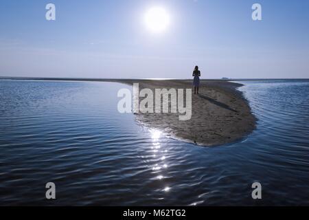 Retro della giovane donna in piedi da solo sulla piccola isola di sabbia staring al tramonto in Koh Phangan, Thailandia. Foto Stock